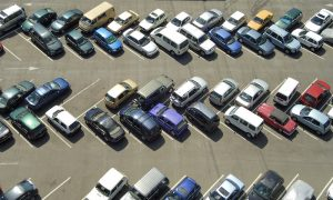 dozens of cars parked in parking lot aerial view
